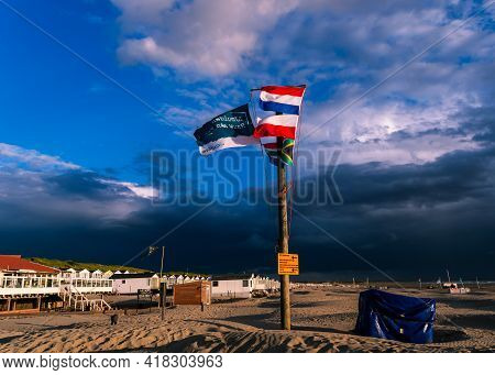Ijmuiden Beach, The Netherlands August 23, 2020:wooden Flagpole With The Polish, Dutch And The Brazi