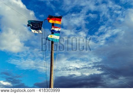 Wooden Flagpole With The German, Dutch And The Argetina Flag. And The Welcome Flag Of The Little Dut