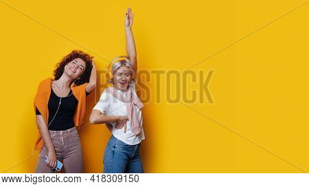 Cheering Curly Haired Sister Are Listening To Music On A Yellow Studio Wall With Free Space
