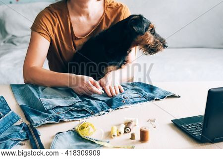 A Woman With Pet In Her Arms Sews Clothes For Dog And Watches Lesson Online Laptop. Diy Reuse Recycl