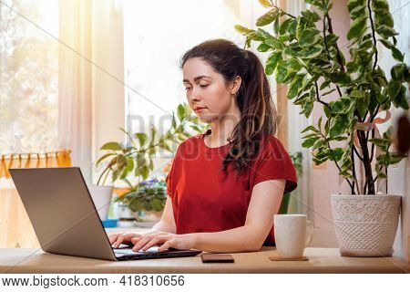 Freelance.a Young, Pretty Woman Is Typing On A Laptop While Sitting At Her Desk. Home Decor, The Sun