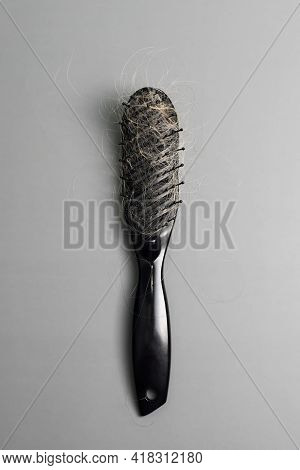 Hair Loss Problem, Hairbrush With A Lot Of Fallen Hairs On Grey Background. Bunch Of Blonde Hair On