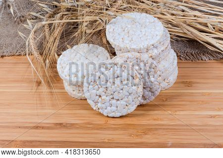 Dry Round Puffed Crispbreads Made Of Different Cereals On Background Of Various Cereal Ears On A Woo