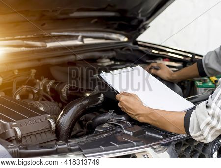 Automobile Mechanic Repairman Checking A Car Engine With Inspecting Writing To The Clipboard The Che