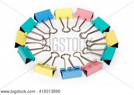Multi Colored Metal Binder Clips Laid Out By Circle On A White Background, Close-up