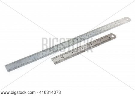 Two Stainless Steel Measuring Rulers With Standard Scales In Millimeters And Inches On A White Backg