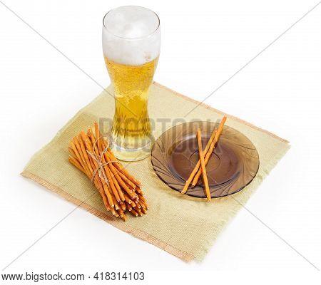 Bundle Of Long Salty Crunchy Pretzels Sticks And Several Sticks On Saucer And Glass Of Lager Beer On