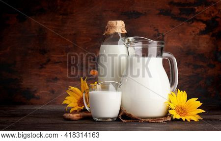 Milk in bottle, jug and glass. In front of wooden background. With copy space