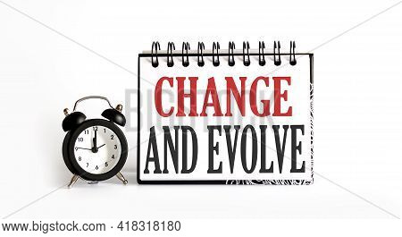 Change And Evolve Notepad Writing On White Background With Alarm Clock