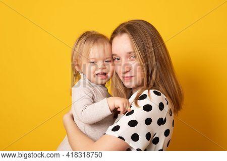 Cute Big Sister Admiring Her Baby Sister. Adorable Teen Girl Holding Her New Baby Girl Sister. Kids