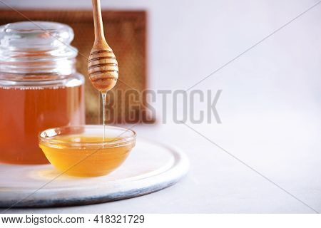 Honey Dripping From Wooden Honey Spoon In Jar On Grey Background. Copy Space. Autumn Harvest Concept