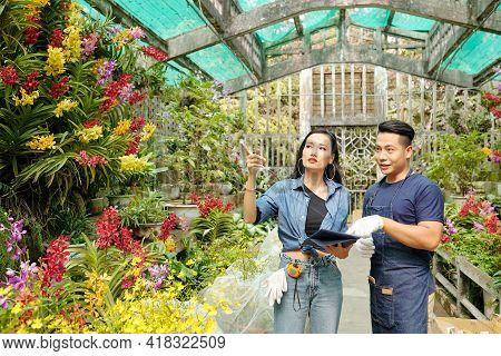 Young Asian Greenhouse Workers Searching For Certain Plants In Greenhouse And Collecting Big Order F