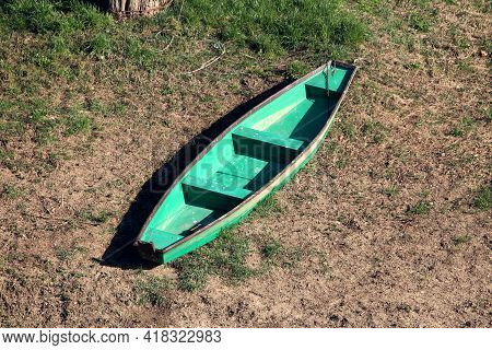 Elongated Light Green With Dark Brown Edge Wooden River Boat Left On Grass And Dry Soil Covered Rive
