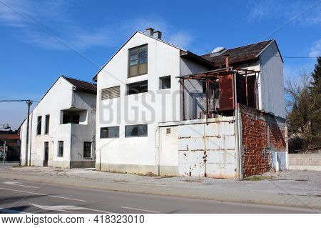 Large Abandoned Suburban Family House With Cracked Dilapidated White Facade And Rusted Sliding Metal