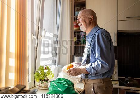 Senior man in kitchen at home looking out of window