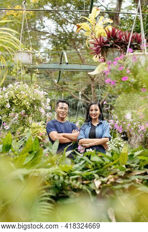 Happy Young Asian Greenhouse Owners Standing In Greenhouse With Plants And Flowers Around