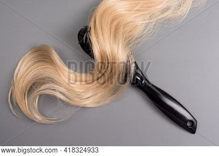 Hairdresser Professional Hairbrush With Curl Of Blonde Hair On Grey Background. Healthy Long Blond H