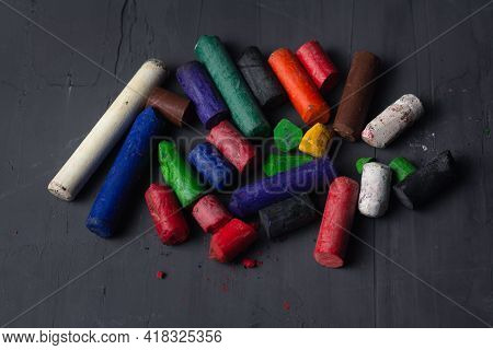 Collection Of Old Colorful Wax Crayons On Black Background. Artistic Background For Designs And Post