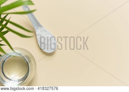 Collagen Powder In A Spoon And A Glass Of Water On A Beige Background With A Copy Space. Extra Prote