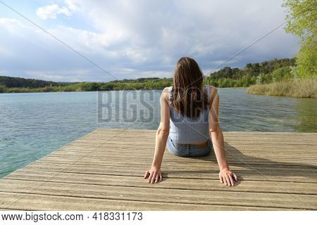Back View Portrait Of A Woman Sitting Relaxing In A Lake Pier On Summer Vacation