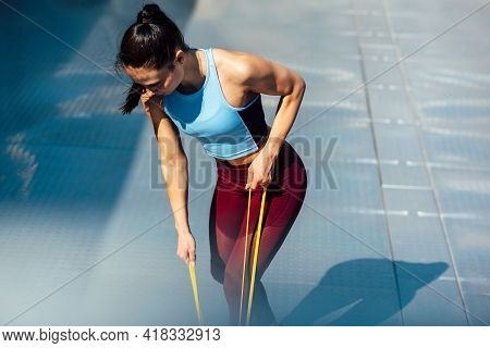 Athelte Female Working With Elastic Band Outside On Grey Background. Healthy Fit Woman Exercising Wi