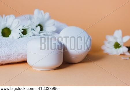 White Cosmetic Tubes With Face Cream, Body Lotion Or Cleanser On A Beige Background With White Flowe