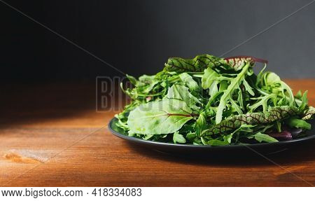 Mix Of Fresh Green Salad Leaves With Arugula, Lettuce, Spinach And Beets On Wooden Rustic Background