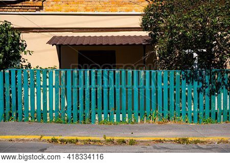 The Old Weathered Wooden Green Fence Near Residential Homes.