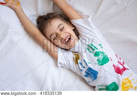 Little Happy Girl With Painted T-shirt Handprints Close Up. Children's Creativity.