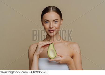 Hygiene Skin Care And Facial Treatments Concept. Indoor Shot Of Pleased Female Model Holds Half Of A