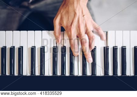 Male Pianist's Hand On Piano Keyboard Seen From Above.music Love