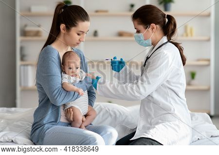 Children Vaccination. Doctor Doing Immunity Strengthening Injection For Newborn Baby At Home