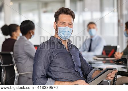 Portrait of successful businessman wearing safety face mask and working on digital tablet in office. Business man using digital tablet while looking at camera and wearing protective face mask.
