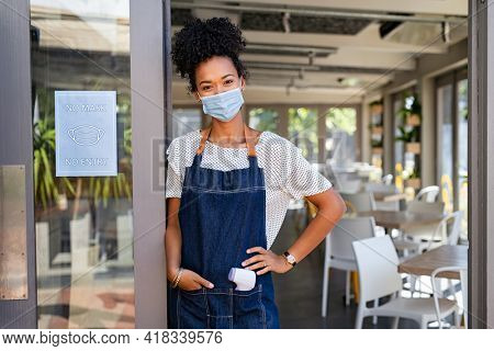 Happy smiling african woman wearing face mask and apron, back to work after quarantine due to covid19. Portrait of black waitress showing sign no mask no entry in her small business shop after covid.