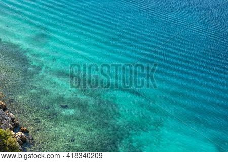 Top view seascape of the rocky coast with shallow water. Turquoise aquamarine colour of the Mediterranean sea water in Turkey