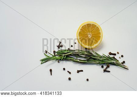 Lemons With Cloves And Fresh Rosemary On White Background. Place For Text.
