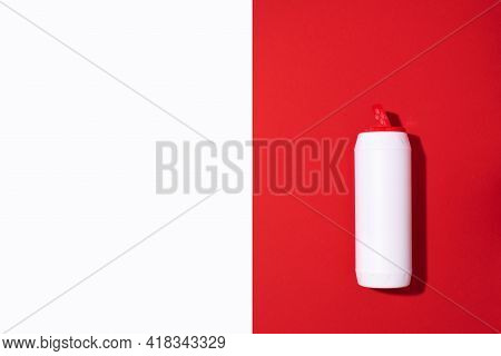 White Plastic Bottle Of Detergent Powder Or Cleaning Agent On Red Background. Copy Space. Top View.