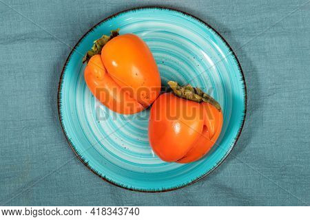 Top View Two Ugly Orange Persimmons On Turquoise Plate On Dark Turquoise Textile Background Close Up