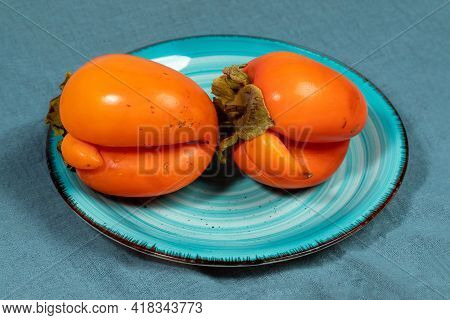 Turquoise Plate With Two Ugly Orange Persimmons On Dark Turquoise Textile Napkin Close Up.