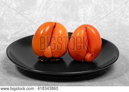 Two Ugly Ripe Orange Persimmons On Black Plate On Light Grey Textured Backdrop Close Up.