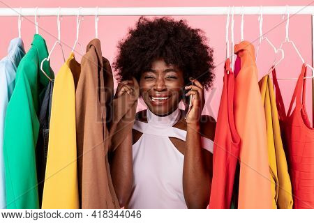 African Shopaholic Woman Crying Talking On Phone Over Pink Background