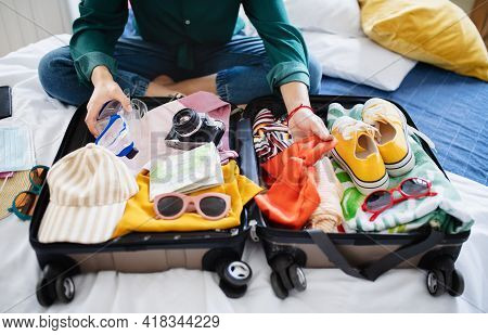 Unrecognizable Woman With Suitcase Packing For Holiday At Home, Coronavirus Concept.