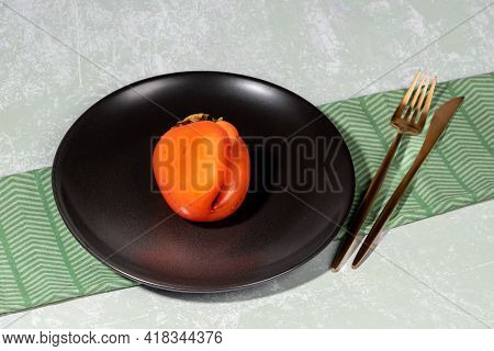 One Ugly Orange Persimmon On Black Plate And Golden Cutlery On Napkin On Light Backdrop.
