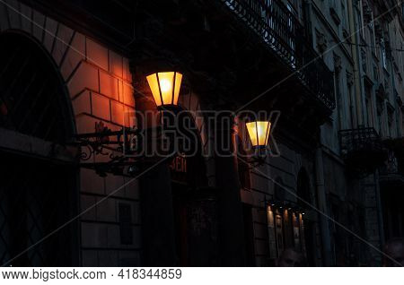 Two Vintage Antique Lanterns Attached To Wall On Beautiful Wrought Iron Holders, In Dark Building Is