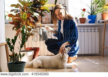 Young woman florist taking care of pot plants indoors, sitting on a floor with her dog, watering flowers