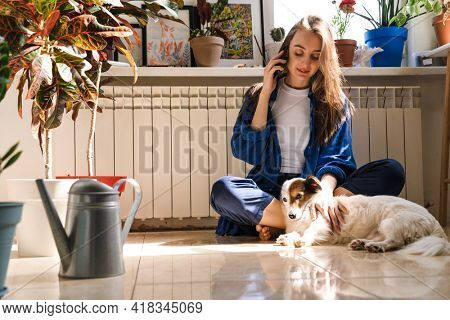 Young woman florist taking care of pot plants indoors, sitting on a floor with her dog, using mobile phone
