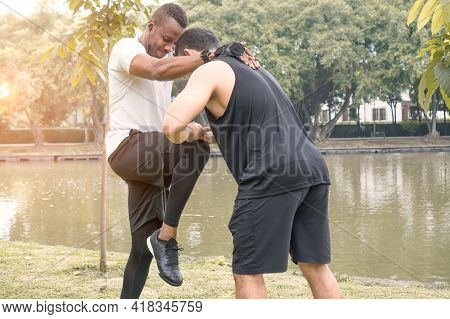 Two Handsome Muscular Men Exercising Together By  River In  Green Forest Park. Asian Trainer Is Trai