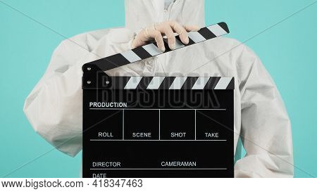 Black Clapperboard Or Movie Clapper Board.woman Wear Face Mask And Ppe Suit On Mint Green Or Tiffany