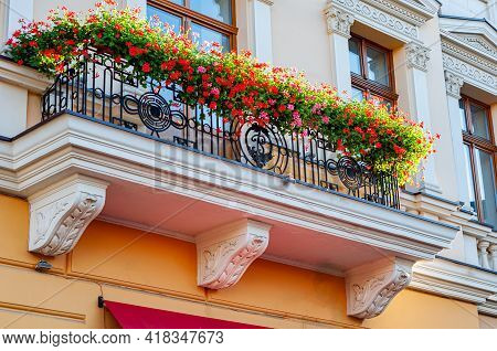 Beautiful Balcony On Old Building, Balcony With Wrought-iron Fence And Bright Red And Purple Flowers