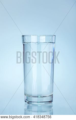Clear Glass Beaker Filled With Water With A Reflection On A Cold Blue Background A Water Utensil Ite